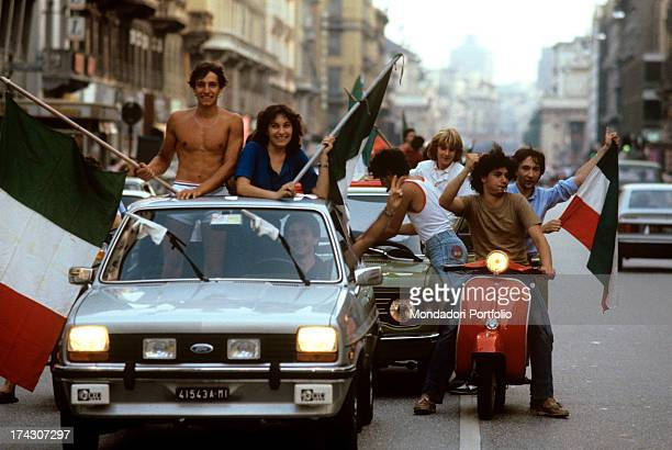 The Italian celebrating the win of the national football team at 1982 FIFA World Cup Some young people on cars and mopeds wave Italian flags Italy...
