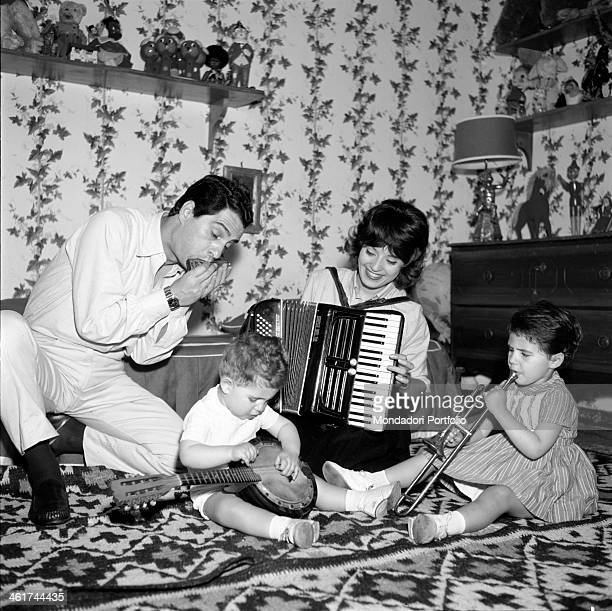 The Italian comic actor Nino Manfredi with his wife Erminia Ferrari and their children Luca Manfredi and Roberta Manfredi are seated on a carpet and...