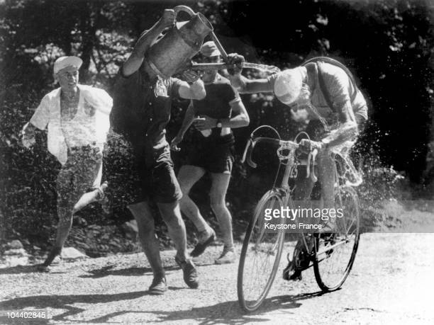 The Italian cyclist Fausto COPPI leader of the 1952 Tour de France being drenched with water by some of the spectators