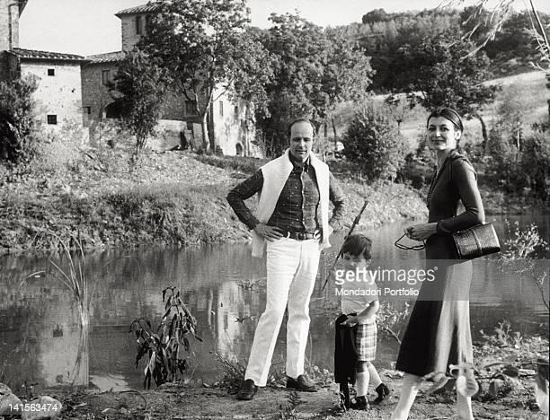 The Italian dancer Carla Fracci her husband Beppe Menegatti and their son Francesco walk along the banks of a stream in their farm Tuscany 1972