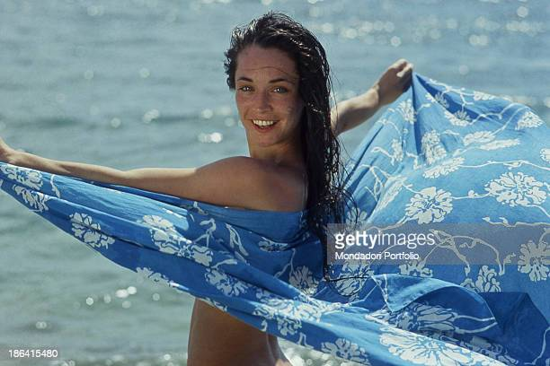 The Italian dancer Oriella Dorella smiles posing with a sarong on a beach in Tahiti French Polynesia Tahiti 1981
