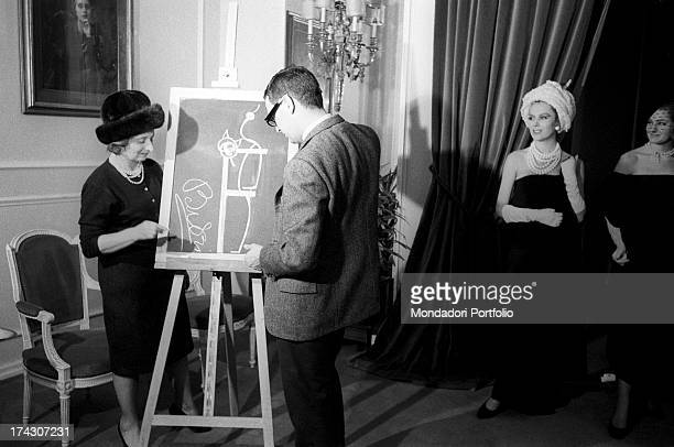The Italian designer Elvira Leonardi Bouyeure artistic name Biki together with her soninlaw shows a drawing on the blackboard in front of two models...