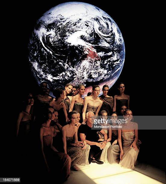 The Italian designer Giorgio Armani, crouching on the catwalk, surrounded by many models. Behind them the image of the globe. Italy, 1990.