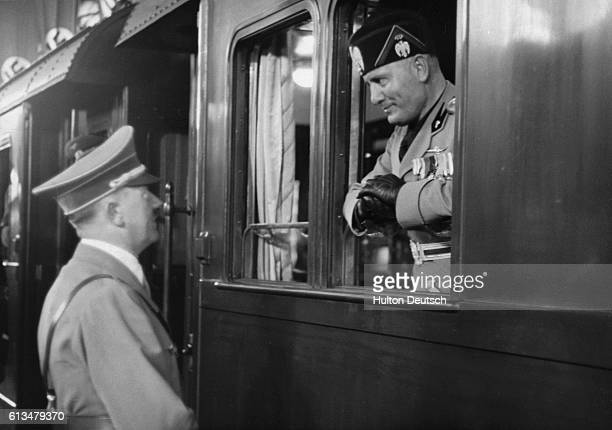 The Italian dictator Benito Mussolini is seen off in his armoured train from Berlin by his German counterpart Adolf Hitler at the end of his 1937
