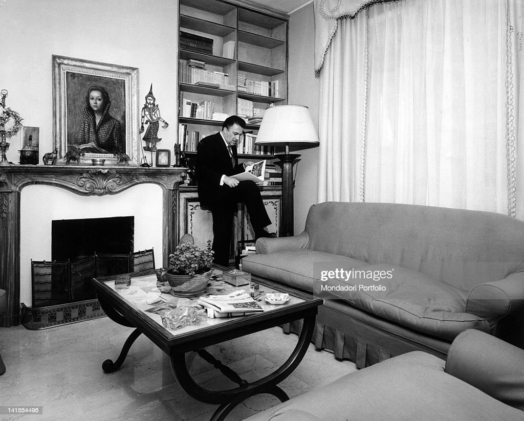 The Italian director Federico Fellini reading a book in the living room of his home. Rome, 1962