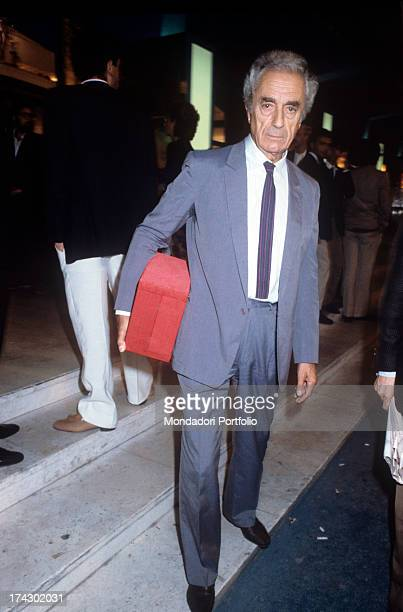 The Italian director Michelangelo Antonioni carries under his arm and closed in a box the Golden Lion lifetime achievement award received at the 40th...