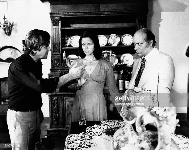 The Italian director Paolo Cavara talking with the Italian actors Agostina Belli and Turi Ferro on the set of the film Virility Rome 1974