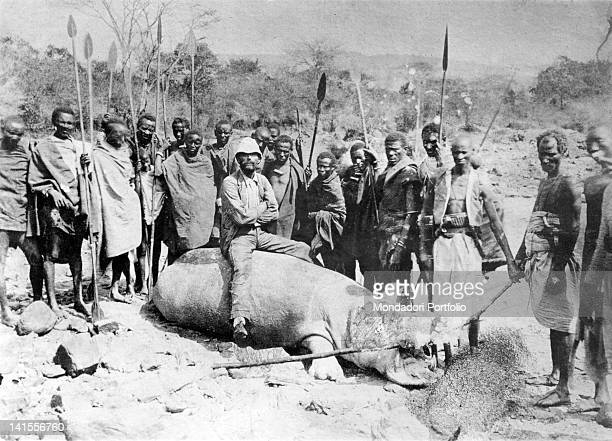 The Italian explorer Vittorio Bottego surrounded by local people armed with spears posing seated on a hippopotamus killed along the banks of the Juba...
