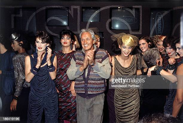 The Italian Fashion designer Ottavio Missoni applauds on the catwalk at the end of a fashion show, followed by several models.