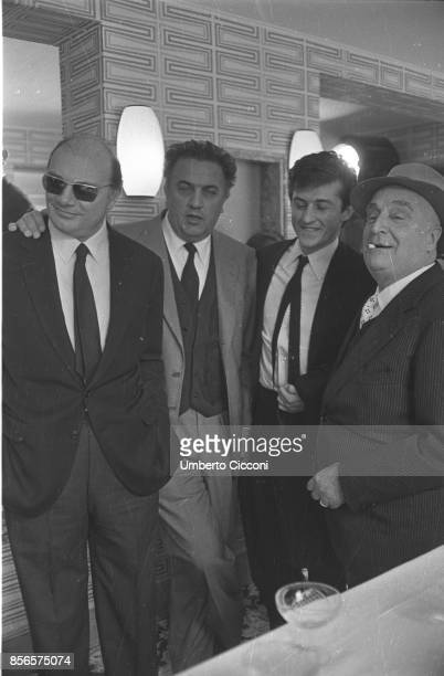 The Italian film director Federico Fellini is at the Sala Palatino for a cocktail party in Rome with the film director Francesco Rosi the Italian...