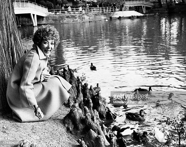The Italian film theatre and television actress Lauretta Masiero is laughing while she is feeding the ducks of the lake of Margherita Gardens in...