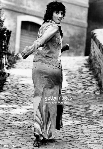 The Italian film theatre and television actress Paola Pitagora seen from her back while walking on a paved road the actress is joking and showing her...