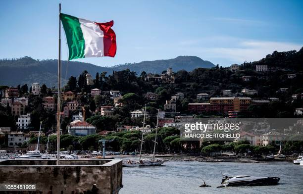 The Italian flag flies over the harbour of Rapallo near Genoa on October 30 2018 after a storm hit the region and destroyed a part of the dam the...