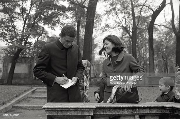 The Italian football player Gigi Riva signing an autograph for a fan in a park of Lombardy Italy 1968