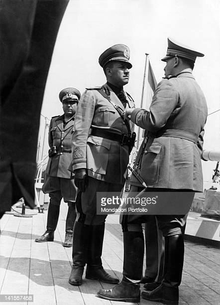 The Italian Foreign Minister Galeazzo Ciano talks with two of his officers on the bridge of the cruiser Almirante Cervera during a trip from San...