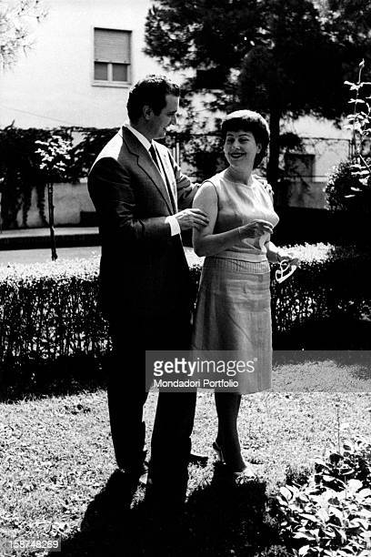 The italian Franco Corelli, born Dario Corelli, and his wife Loretta smiling at each other into the garden of a courtyard in Verona; the famous...