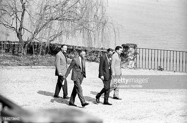 The Italian industrialist Gianni Agnelli walking along with other Italian industrialists along the avenues of the Villa d'Este during the Meeting of...
