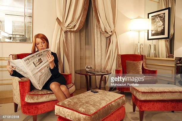 The Italian Minister of Tourism Michela Vittoria Brambilla seats on a red sofa reading a newspaper in the suite of the Savoia Hotel where she resides...