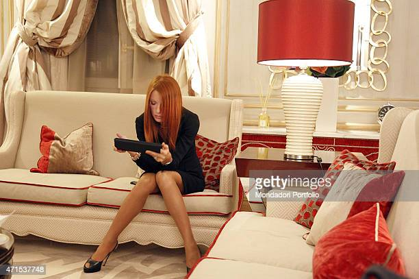 The Italian Minister of Tourism Michela Vittoria Brambilla seats on a red sofa with a tablet in her hands in the suite of the Savoia Hotel where she...