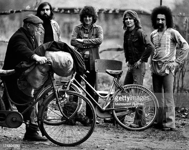 The Italian music band I Camaleonti is posing behind a parked bicycle and an old man pushing his bicycle from left Paolo de Ceglie Antonio Cripezzi...