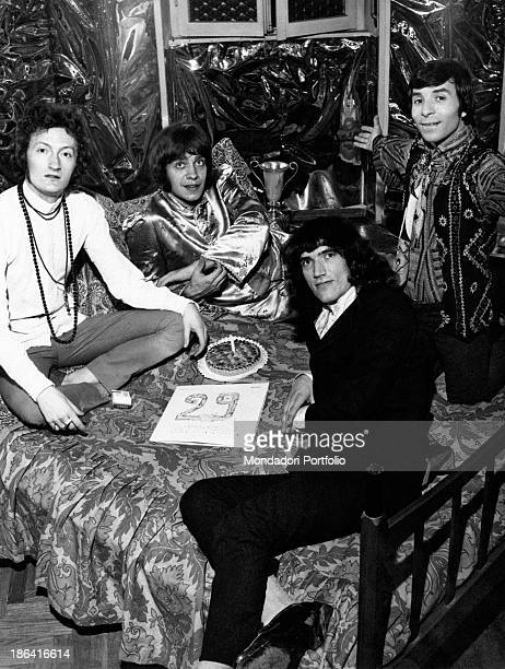 The Italian music group Equipe 84 seated on a bed is celebrating around a cake in the centre a sheet of paper with the number 29 the band has reached...