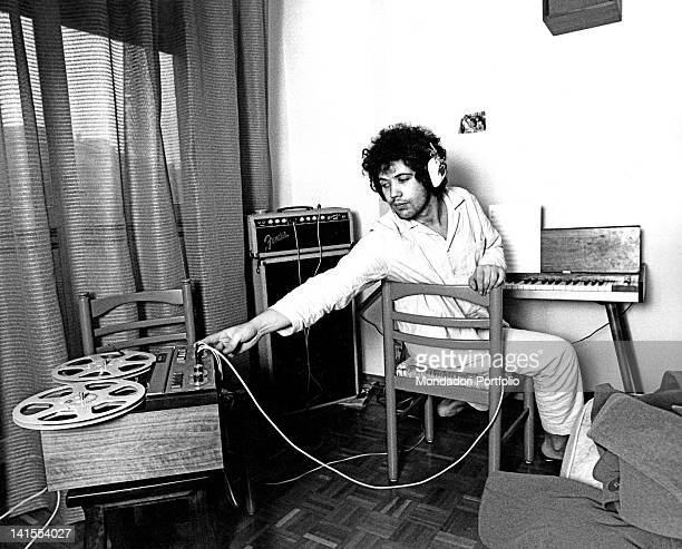 The Italian musician and singersongwriter Lucio Battisti listening to music with headphones wearing pyjamas in his house Milan 1970