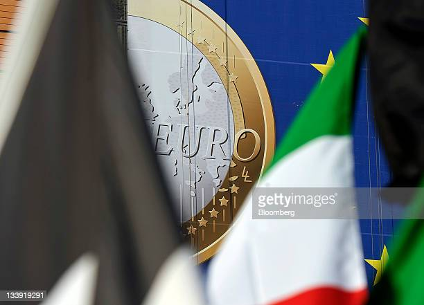 The Italian national flag right is seen against a giant euro banner featuring an image of a euro coin which hangs on the side of the headquarters of...