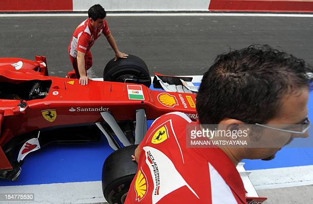 The Italian Navy ensign is seen in between the front wheels of Ferrari driver Fernando Alonso of Spain's car as pit crew work during the first...