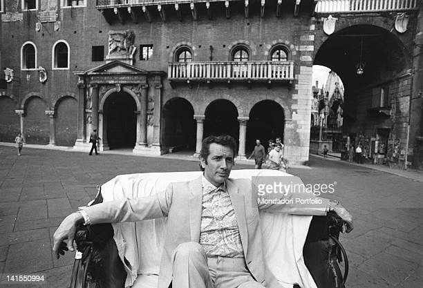 The Italian opera singer Franco Corelli sitting on a armchair in Piazza delle Erbe. Verona, July 1970