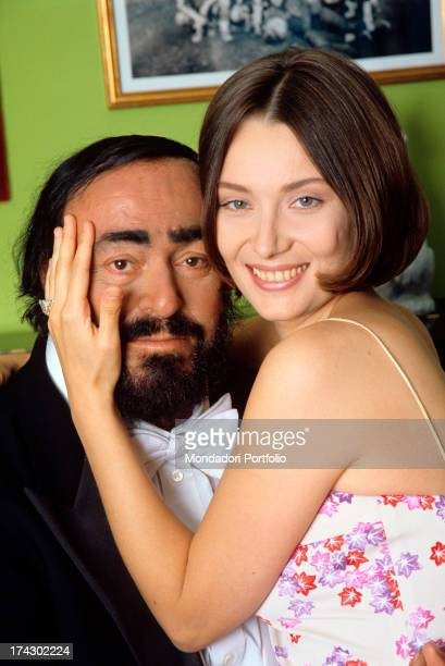 The Italian opera singer Luciano Pavarotti poses for the photograper while he holds his second wife in his arms, Nicoletta Mantovani, who carresses...
