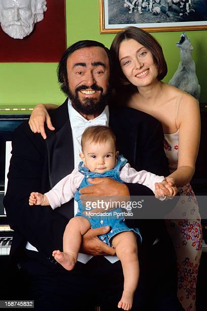 The Italian opera singer Luciano Pavarotti poses smiling for the photographer, holding his daughter Alice in his arms and with his second wife...