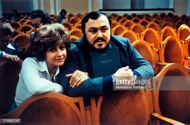The Italian opera singer Luciano Pavarotti sitting in a theatre seat holding the opera book of Verdi's Requiem next to him is his first wife Adua...