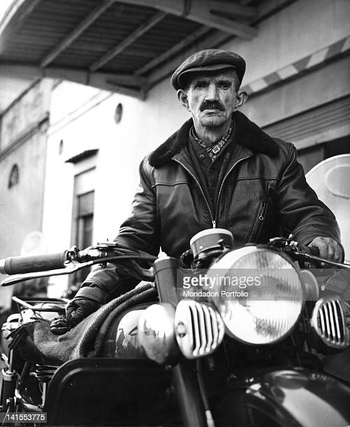 The Italian painter Antonio Ligabue posing next to his favourite motorcycle: a Moto Guzzi 500. Reggio Emilia, March 1961