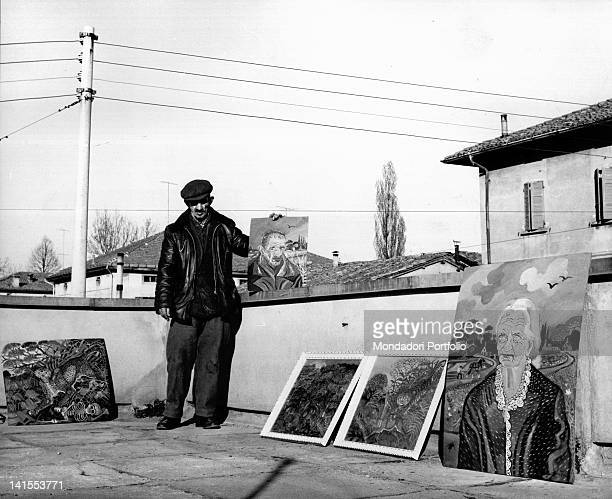The Italian painter Antonio Ligabue posing on the terrace of a friend with some of his paintings. Reggio Emilia, March 1961