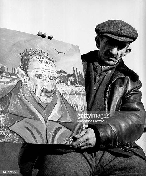 The Italian painter Antonio Ligabue posing with a self-portrait. Reggio Emilia, March 1961