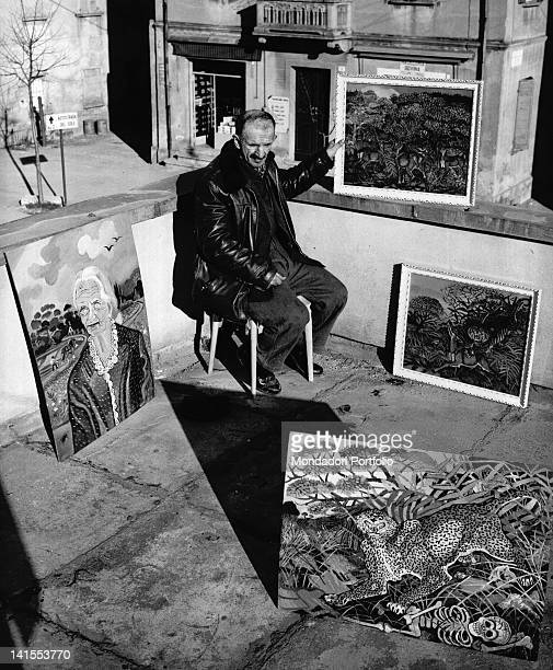 The Italian painter Antonio Ligabue sitting on the terrace of a friend with some of his paintings. Reggio Emilia, March 1961