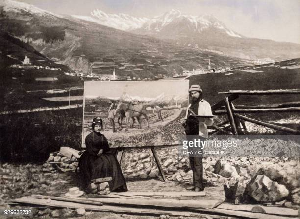 The Italian painter Giovanni Segantini and his wife Bice in front of the painting Plowing photograph from ca 1890 19th century