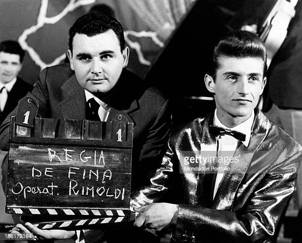 The Italian pianist arranger and conductor Pino Calvi is posing next to the song writer Tony Renis in front of the ciak of the broadcast Milano di...