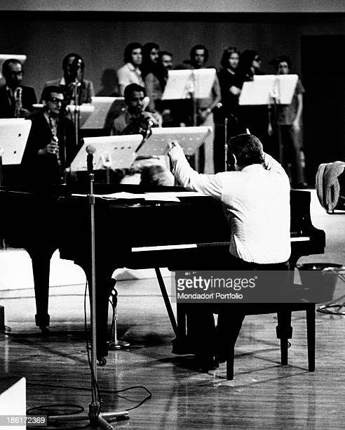 The Italian pianist conductor and composer Pino Calvi is conducting an orchestra at the rehearsals for the variety show titled Senza Rete broadcast...