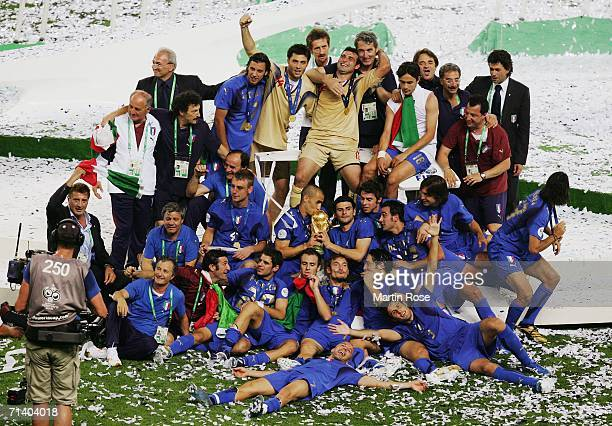 The Italian players and coaching staff celebrate with the World Cup trophy following their victory in a penalty shootout at the end of the FIFA World...
