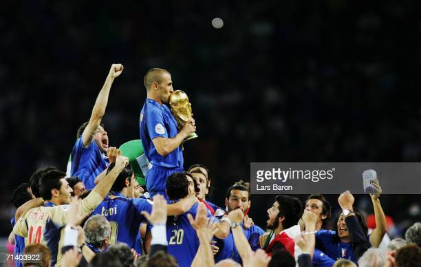 The Italian players celebrate as Fabio Cannavaro of Italy kisses the World Cup trophy following victory in a penalty shootout at the end of the FIFA...