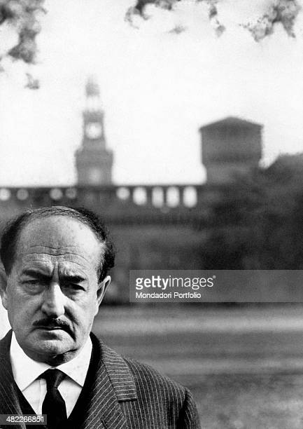 The Italian poet Salvatore Quasimodo elegantly dressed with jacket and tie is posign in front of the photographer with a serious expression behind...