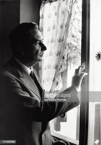 The Italian politician and secretary of the DC Aldo Moro looking out the window in his holiday house Cortina d'Ampezzo December 1962