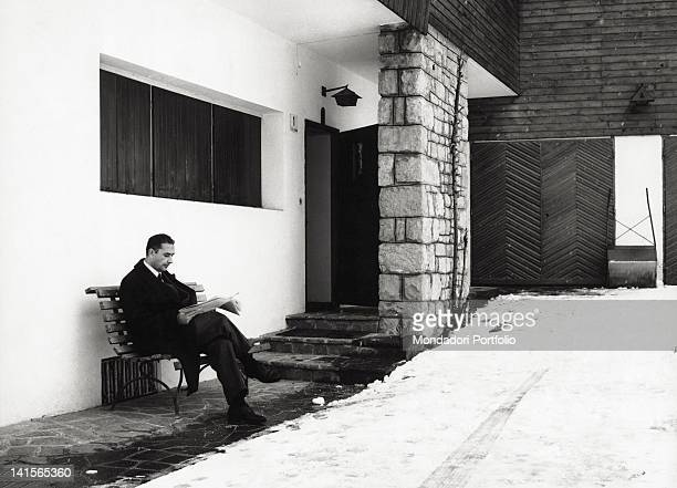 The Italian politician and secretary of the DC Aldo Moro reading the newspaper on holiday seated on a bench Cortina d'Ampezzo December 1962