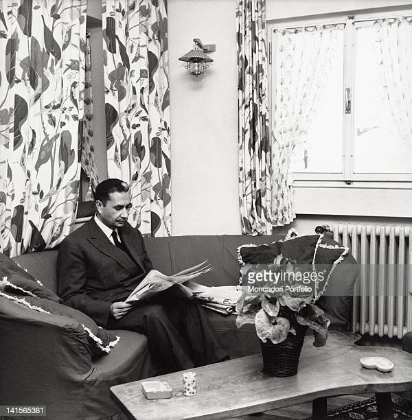 The Italian politician and secretary of the DC Aldo Moro reading the newspaper seated on the sofa of his holiday house Cortina d'Ampezzo December 1962