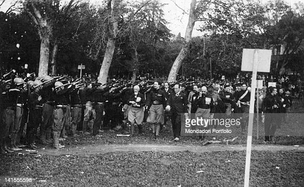 The Italian politician Benito Mussolini inspecting a large group of fascists who salute with their arm outstretched at the Villa Borghese Rome 30th...