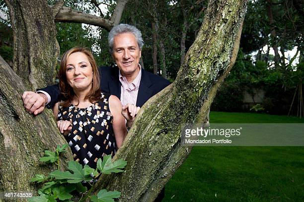 The Italian politician Francesco Rutelli and the Italian journalist Barbara Palombelli smiling rest on a tree in the garden of their home Italy April...