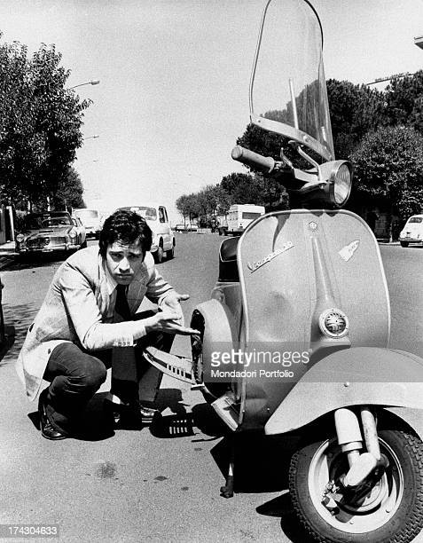The Italian popular actor for theater and cinema Enrico Montesano is joking with the photographer he is next to his Vespa scooter pretending it is...