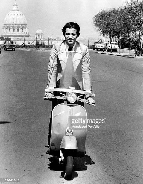 The Italian popular actor for theater and cinema Enrico Montesano standing on a Piaggio Vespa scooter on a street of the Italian capital city; behind...