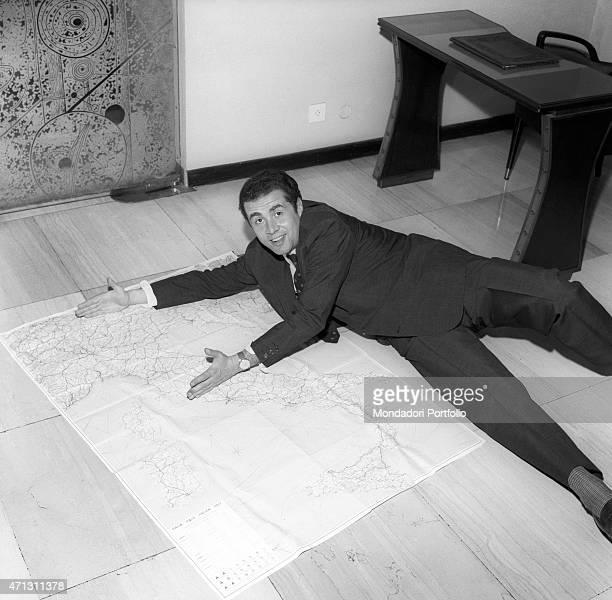 The Italian presenter Enzo Tortora jokes lying on the ground on a map of Italy Milan 1967